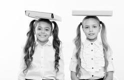 Estudos e aprendizagem As meninas felizes das crianças mantêm pastas de arquivos na cabeça os estudos e a aprendizagem das crianç foto de stock