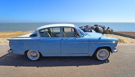 Estupendo azul claro cl?sico motor de la moza descarada de Hillman aparcamiento en la 'promenade' de la orilla del mar imagenes de archivo