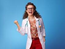 Esultanza felice della donna del pediatra sul blu fotografia stock
