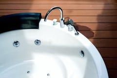 Esvazie a banheira branca do redemoinho com o torneira no assoalho de madeira fotos de stock royalty free