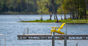 Esvazie a cadeira de plataforma amarela em uma doca no lago Fotos de Stock Royalty Free