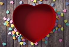 Esvazie coração vermelho a caixa dada forma com mini corações no fundo de madeira Fotografia de Stock Royalty Free
