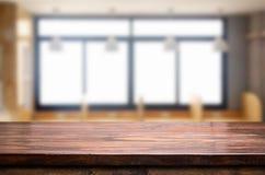 Esvazie do tampo da mesa de madeira no borrão do vidro de janela na manhã b foto de stock