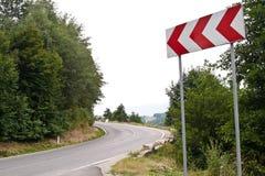 Esvazie a estrada da montanha e o sinal de tráfego curvados Imagens de Stock Royalty Free