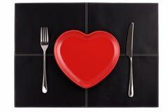 Esvazie a forquilha vermelha da faca da placa do coração no couro preto Foto de Stock
