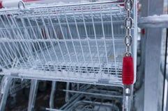 Esvazie o carro de compra com fechamento da moeda e a neve nela Fotografia de Stock