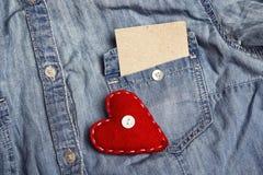 Esvazie o cartão de papel no bolso da camisa da sarja de Nimes e do coração vermelho Copie o sp Imagens de Stock Royalty Free
