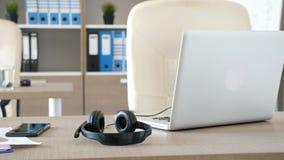 Esvazie o escritório moderno com uma mesa na parte dianteira e em um par de fones de ouvido que encontram-se na tabela vídeos de arquivo