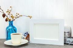 Esvazie o quadro branco da foto com xícara de café e o vaso de vidro azul o Foto de Stock Royalty Free