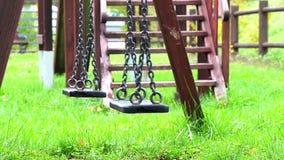 Esvazie os balanços que balançam no campo de jogos para a criança, movido do vento filme