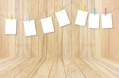 Esvazie os quadros brancos da foto que penduram com os pregadores de roupa na parte traseira de madeira Imagens de Stock Royalty Free