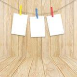 Esvazie os quadros brancos da foto que penduram com os pregadores de roupa na parte traseira de madeira Fotos de Stock