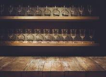 Esvazie a parte superior da tabela de madeira com a barra e vidro bebendo contrários borrados foto de stock