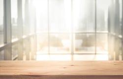 Esvazie a parte superior da tabela de madeira com luz solar do borrão na construção da janela imagens de stock