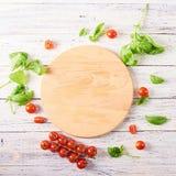 Esvazie a placa de corte de madeira com tomates e manjericão imagem de stock