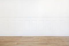 Esvazie a sala branca com assoalho de madeira e a parede aparada madeira Imagem de Stock Royalty Free