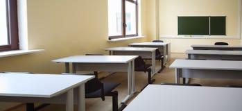Esvazie a sala de aula com mesas da escola e as cadeiras pretas fotografia de stock royalty free