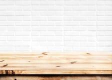 Esvazie a tabela de madeira com fundo branco da parede de tijolo foto de stock