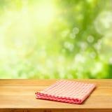 Esvazie a tabela de madeira com toalha de mesa sobre o fundo do bokeh do jardim Imagens de Stock Royalty Free