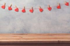 Esvazie a tabela de madeira da plataforma sobre o fundo rústico da parede com a festão da forma do coração Rosa vermelha Imagens de Stock Royalty Free