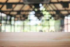Esvazie a tabela de madeira e borre o fundo do sumário na frente de r imagem de stock