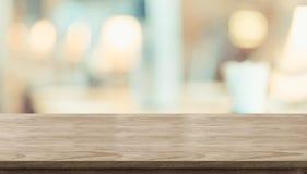 Esvazie a tabela de madeira rústica e a tabela borrada da luz suave no restaura foto de stock