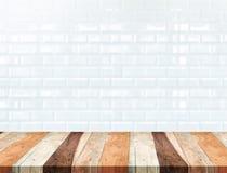 Esvazie a tabela de madeira tropical e borre a parede de tijolo branca do azulejo foto de stock