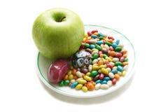 Esverdeie a maçã e doces coloridos na placa branca Imagens de Stock