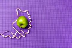 Esverdeie a maçã e a fita de medição Esteira roxa da ioga Imagens de Stock