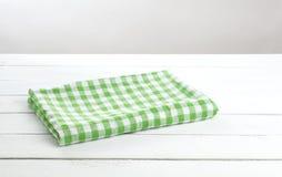 Esverdeie a toalha de mesa dobrada no fundo branco da tabela para a montagem do produto fotos de stock