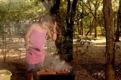 Età elementare della bambina che cucina il evapi del ‡ di Ä sulle gru del barbecue Fotografia Stock Libera da Diritti