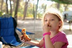 Età elementare della piccola ragazza caucasica che ha un outdoo della prima colazione Immagine Stock