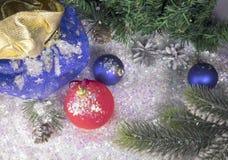 Et boule bleue du ` s de nouvelle année sur la neige décorative et un sac avec le cadeau Images stock