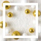 Or et décorations blanches de boule de scintillement dans la neige photos stock