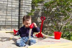 On et le garçon à moitié an joue dans le bac à sable Photo stock