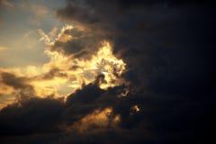 Or et nuages noirs sur le ciel bleu Images stock