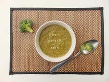 et x22 ; Obtenez un meilleur soon& x22 ; écrit en potage aux légumes avec la cuillère Image stock