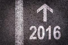 2016 et une flèche écrite sur une route goudronnée Photographie stock libre de droits