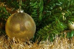 Etail της χρυσής διακόσμησης στο χριστουγεννιάτικο δέντρο με τη χρυσή αλυσίδα. Στοκ Εικόνες