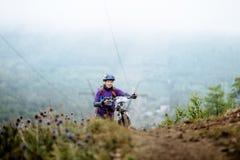 Etapa da elevação do mountainbiker da moça na montanha com bicicleta Fotos de Stock Royalty Free