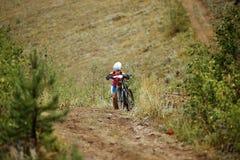 Etapa da elevação do mountainbiker do atleta da menina na montanha com minha bicicleta Foto de Stock