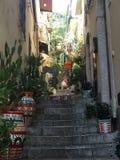 Etapas da rua secundária de Taormina com os potenciômetros cerâmicos em Sicília foto de stock