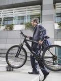 Etapas de Carrying Bicycle Up do homem de negócios Imagem de Stock