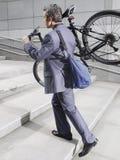 Etapas de Carrying Bicycle Up do homem de negócios Imagens de Stock