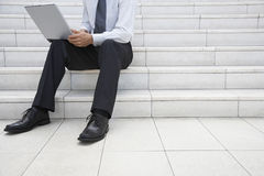 Etapas do escritório de Using Laptop On do homem de negócios Foto de Stock Royalty Free