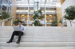 Etapas do escritório de Using Laptop On do homem de negócios Imagem de Stock