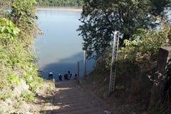 Etapas - para baixo ao rio com medidas da inundação e aos povos que fazem a lavanderia Fotos de Stock Royalty Free