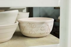 Etched Pottery Bowl on wooden shelf. Clay Pottery Bowl with a design etched on the outside royalty free stock photo
