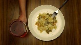 etend deegwaren met vork en drinkend wijn