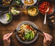 Etend gezonde vegetarische maaltijd in kom met kekerspuree, stoven de geroosterde groenten, rode paprikatomaten, avocado en zaden Royalty-vrije Stock Afbeelding